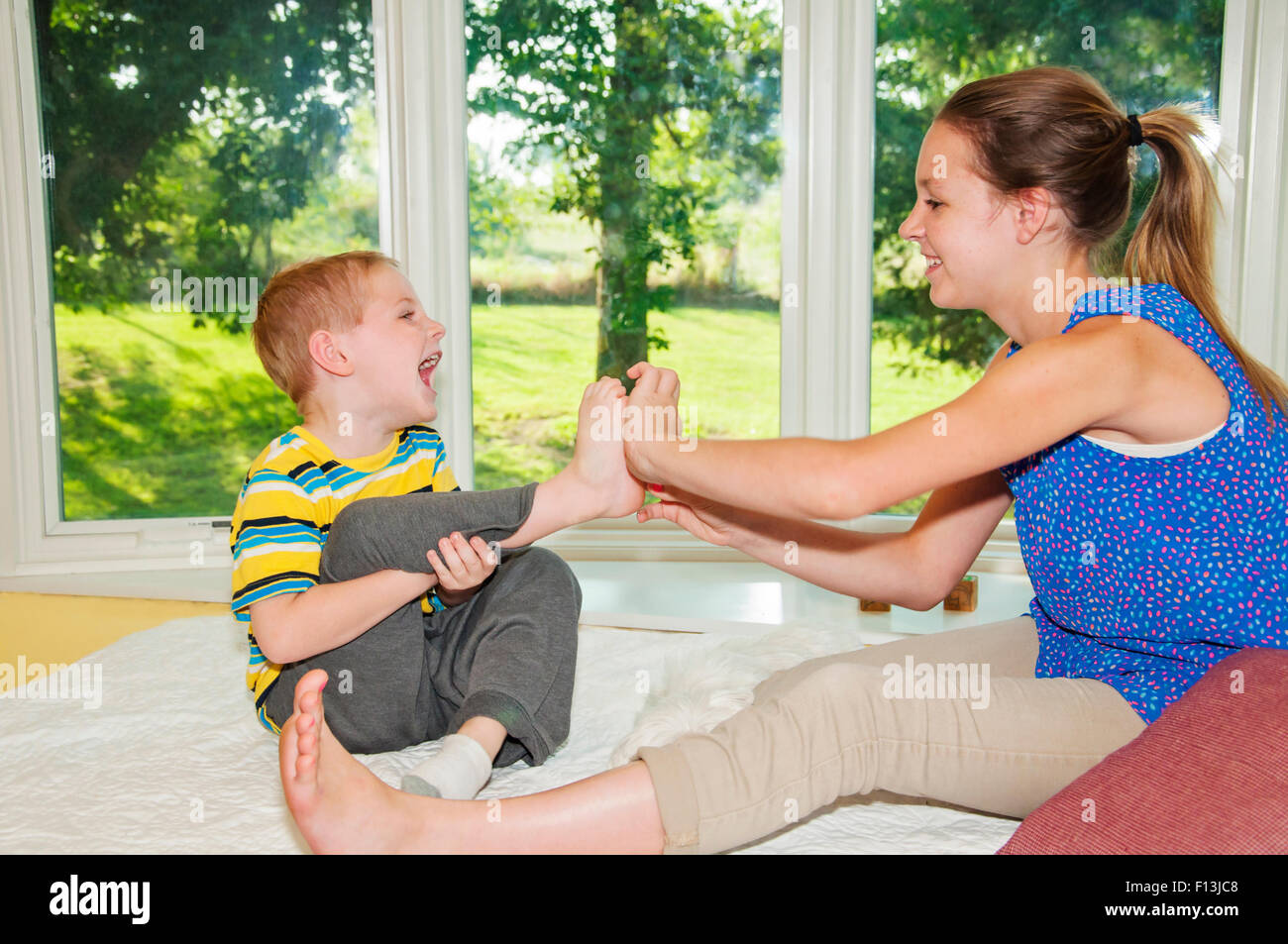 Girl tickles her brothers foot while he laughs - Stock Image