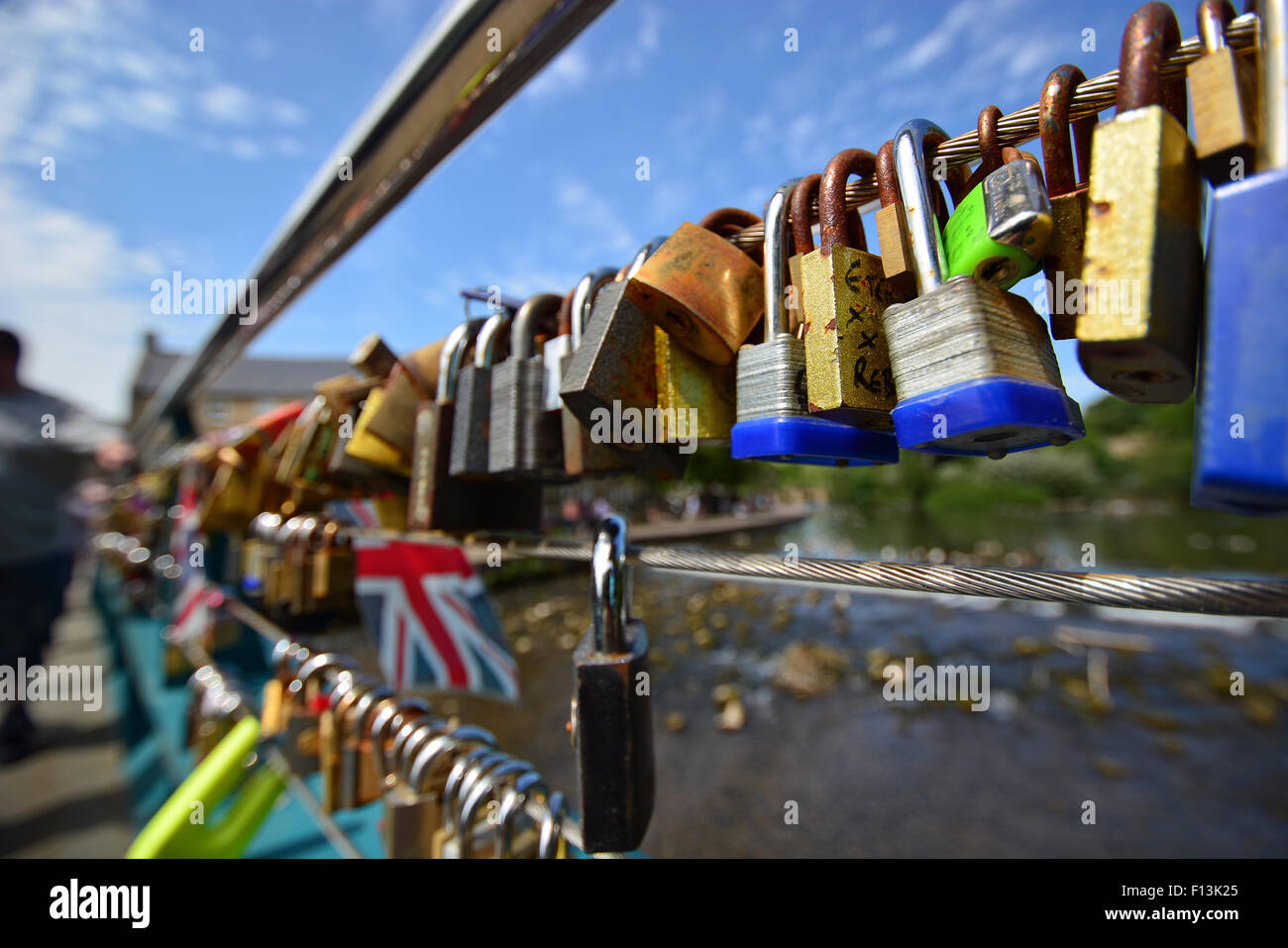 Colourful padlocks inscribed with lovers initials attached to a bridge in the town of Bakewell, Derbyshire. - Stock Image