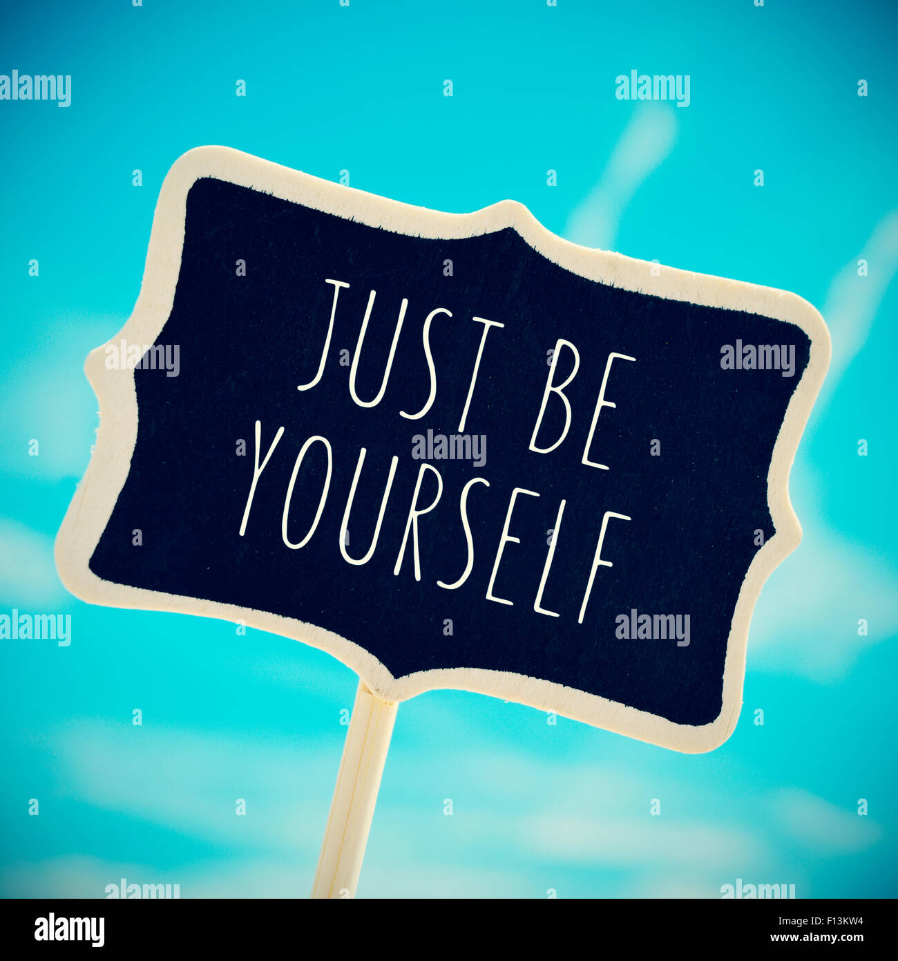 a chalkboard with the text just be yourself written in it against the blue sky, slight vignette added - Stock Image
