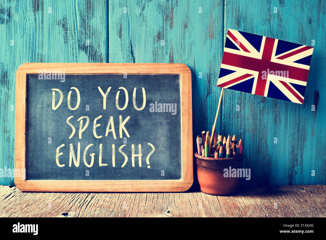 a chalkboard with the text do you speak english? written in it, a pot with pencils and the flag of the United Kingdom, - Stock Image