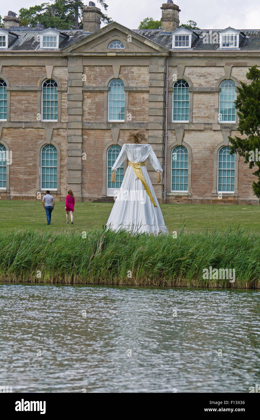 Two visitors walking away from Kern Baby at Compton Verney House; it's a 5 metre corn dolly by the artist Faye - Stock Image