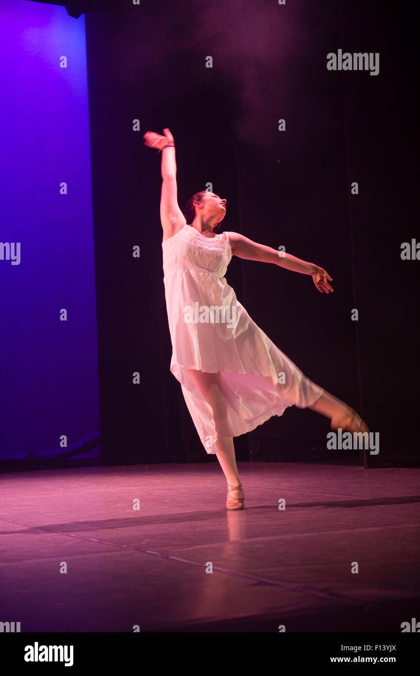 A Young girl student dancer at Aberystwyth Arts Centre  Dance School dancing her solo on stage in an adaptation - Stock Image