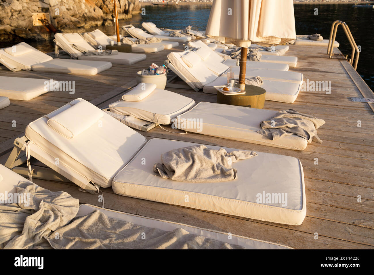 Dirty and used towels are on sunbeds near seaside after the crowded day as a different summer time concept - Stock Image