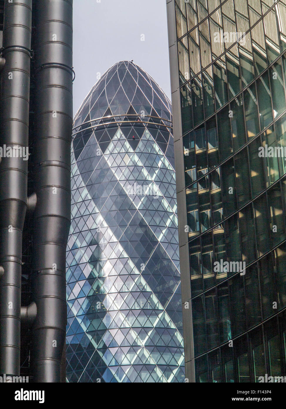 Stormy and sunny slkies light up the Gherkin and the lloyds Building in the City of London and St.andrew Undershaft - Stock Image