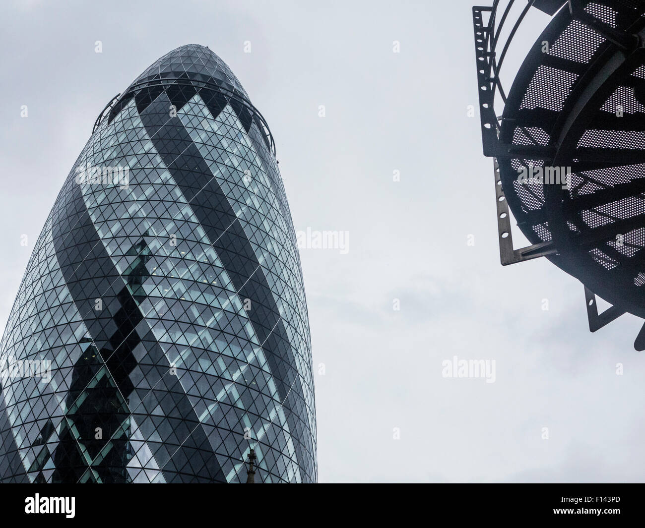 stormy skies and stormy markets over the Gherkin and the city of london financial district - Stock Image