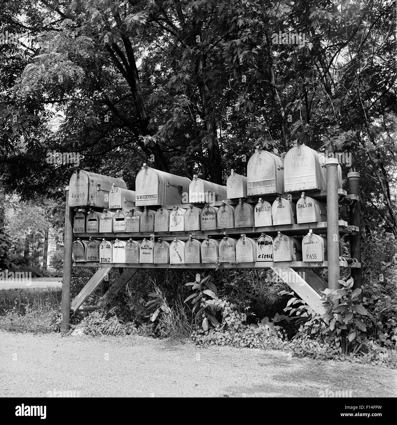 1930s 1940s 1950s GROUP OF 37 RURAL DELIVERY MAILBOXES AT SIDE OF COUNTRY ROAD Stock Photo
