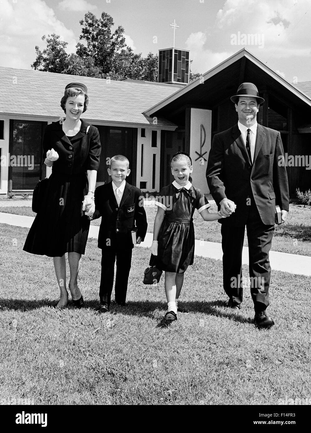 1960s SMILING HAND HOLDING FAMILY OF FOUR MOTHER FATHER SON DAUGHTER WALKING AWAY FROM CHURCH LOOKING AT CAMERA - Stock Image