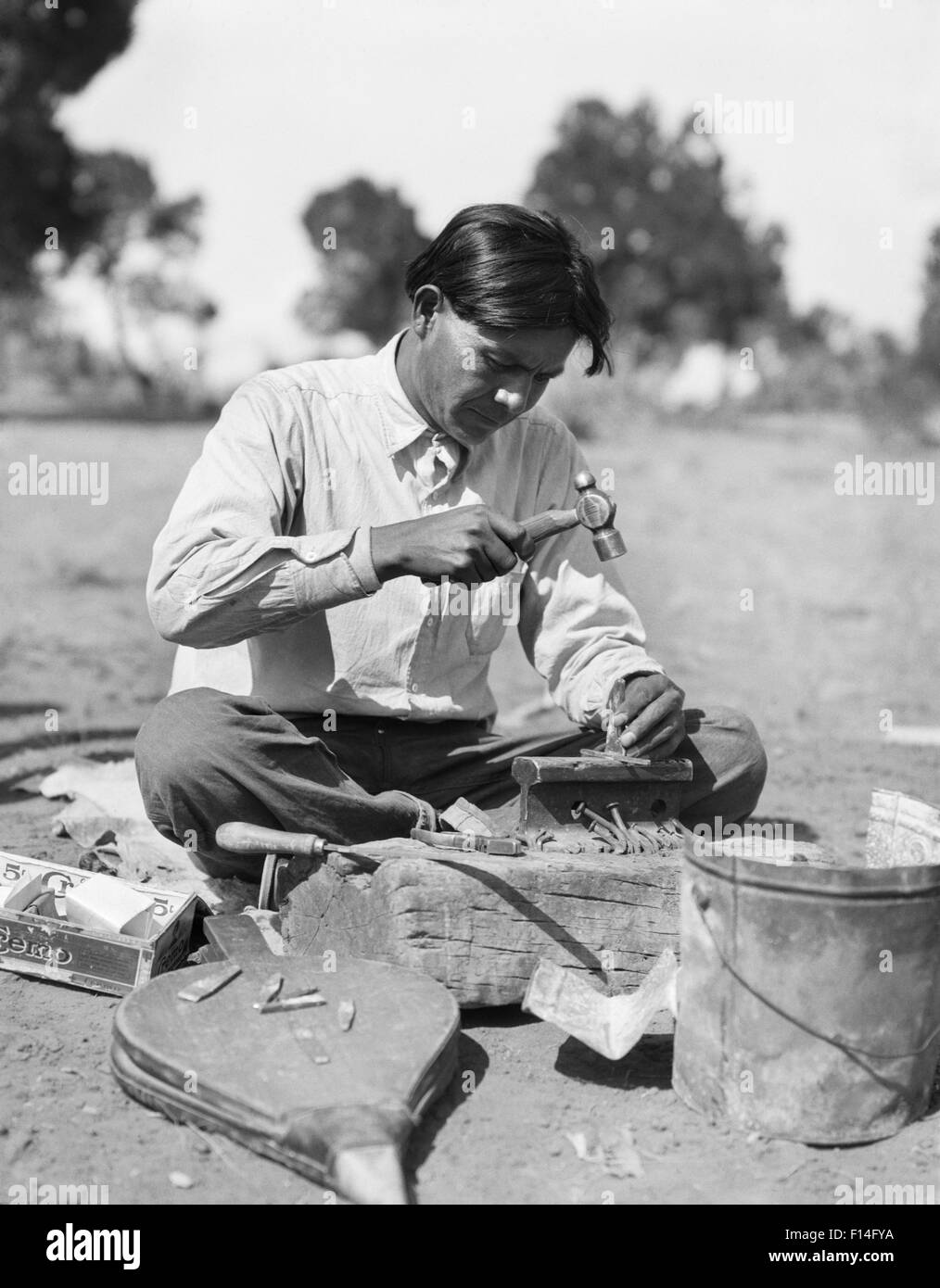 1920s NATIVE AMERICAN INDIAN NAVAJO MAN SILVERSMITH CRAFTSMAN MAKING TRADITIONAL JEWELRY NEW MEXICO USA - Stock Image
