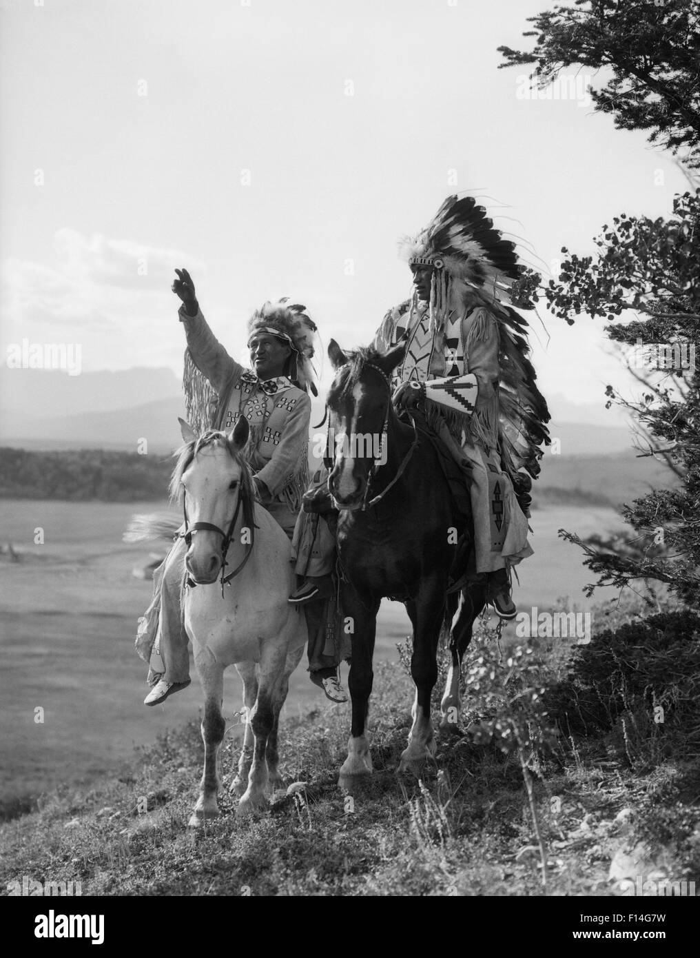 1920s TWO NATIVE AMERICAN INDIAN MEN ON HORSEBACK IN FULL FEATHER HEADDRESS STONEY SIOUX TRIBE ALBERTA CANADA - Stock Image