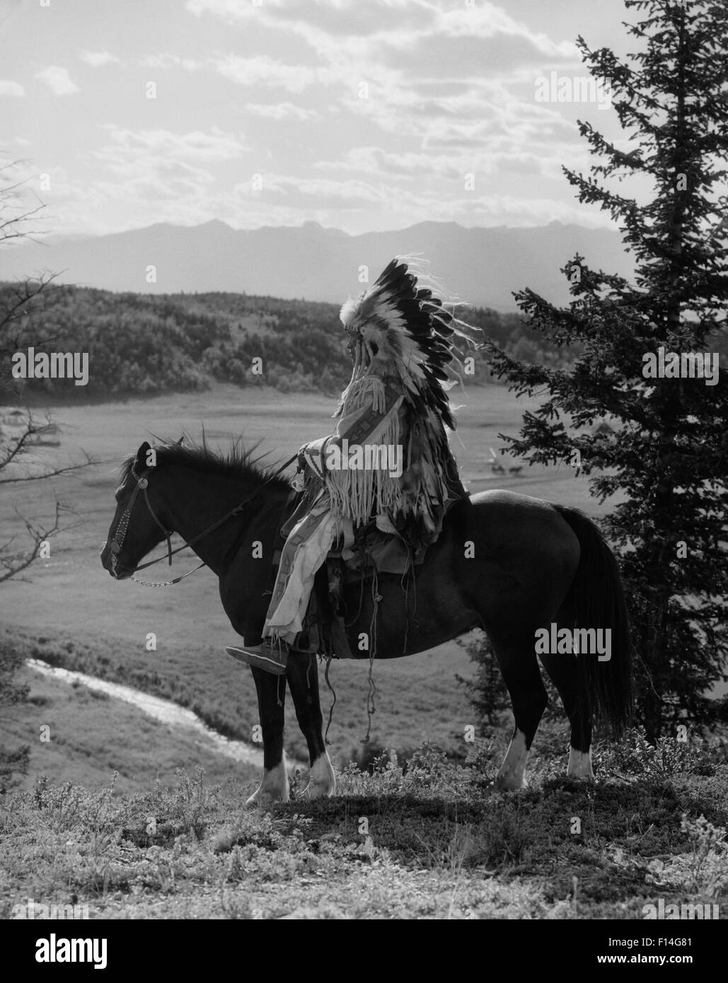 1920s NATIVE AMERICAN STONEY SIOUX MAN FULL EAGLE FEATHER HEADDRESS ON HORSEBACK LOOKING OVER VALLEY ALBERTA CANADA - Stock Image