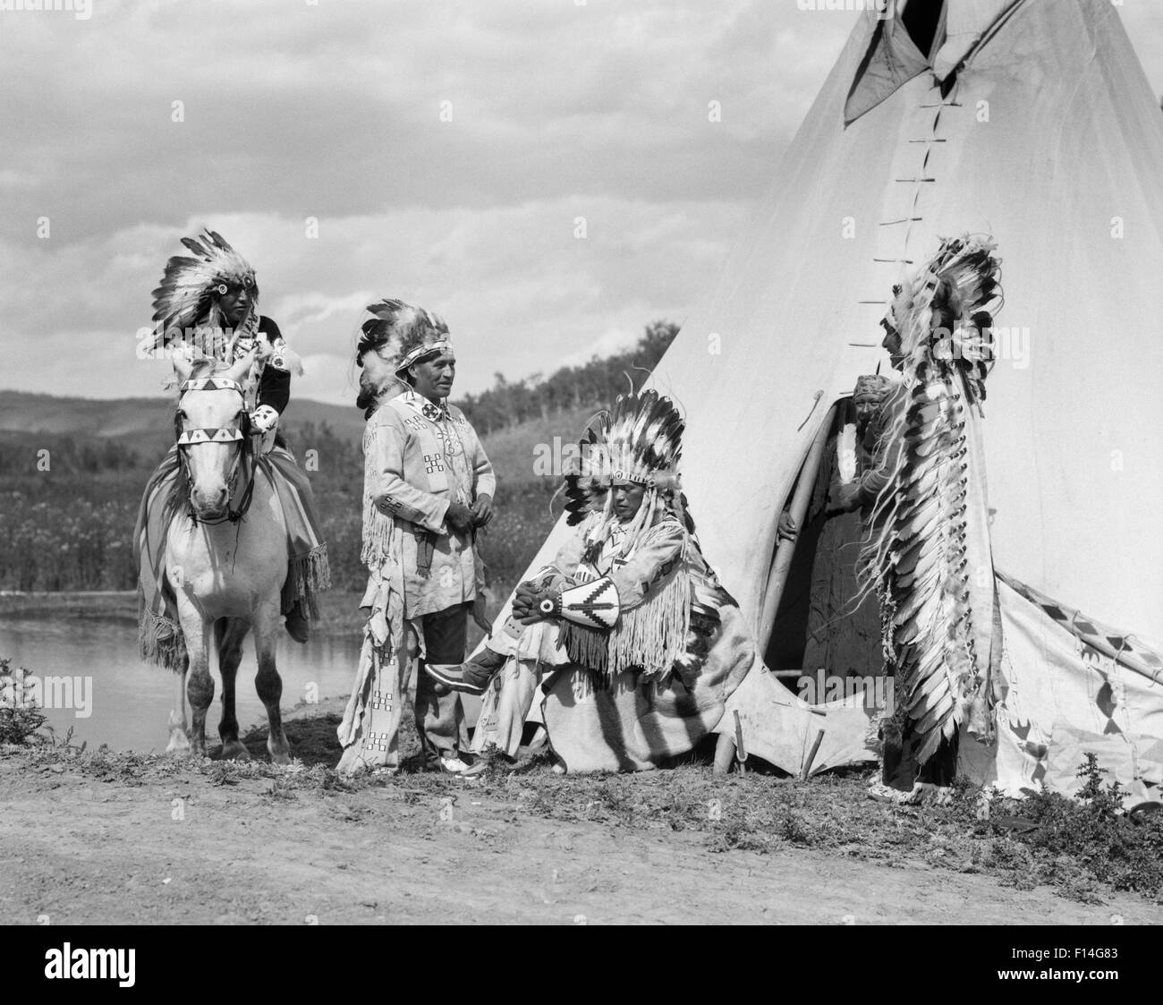 1920s FOUR NATIVE AMERICAN STONEY SIOUX INDIAN MEN ASSEMBLED BESIDE TEPEE WEARING FULL EAGLE FEATHER WAR BONNETS - Stock Image