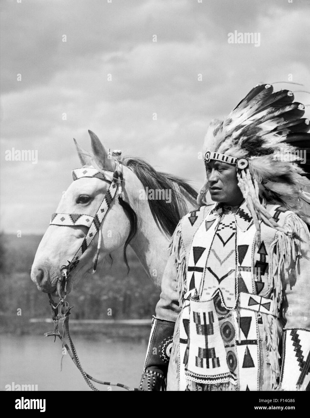 1920s PORTRAIT NATIVE AMERICAN INDIAN CHIEF FULL FEATHER HEADDRESS BEADED CLOTHES HORSE STONEY SIOUX TRIBE ALBERTA - Stock Image