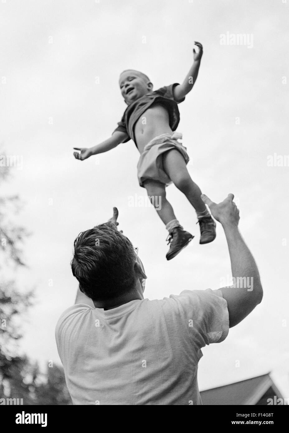 1950s 1960s FATHER TOSSING HIS SON UP INTO THE AIR - Stock Image