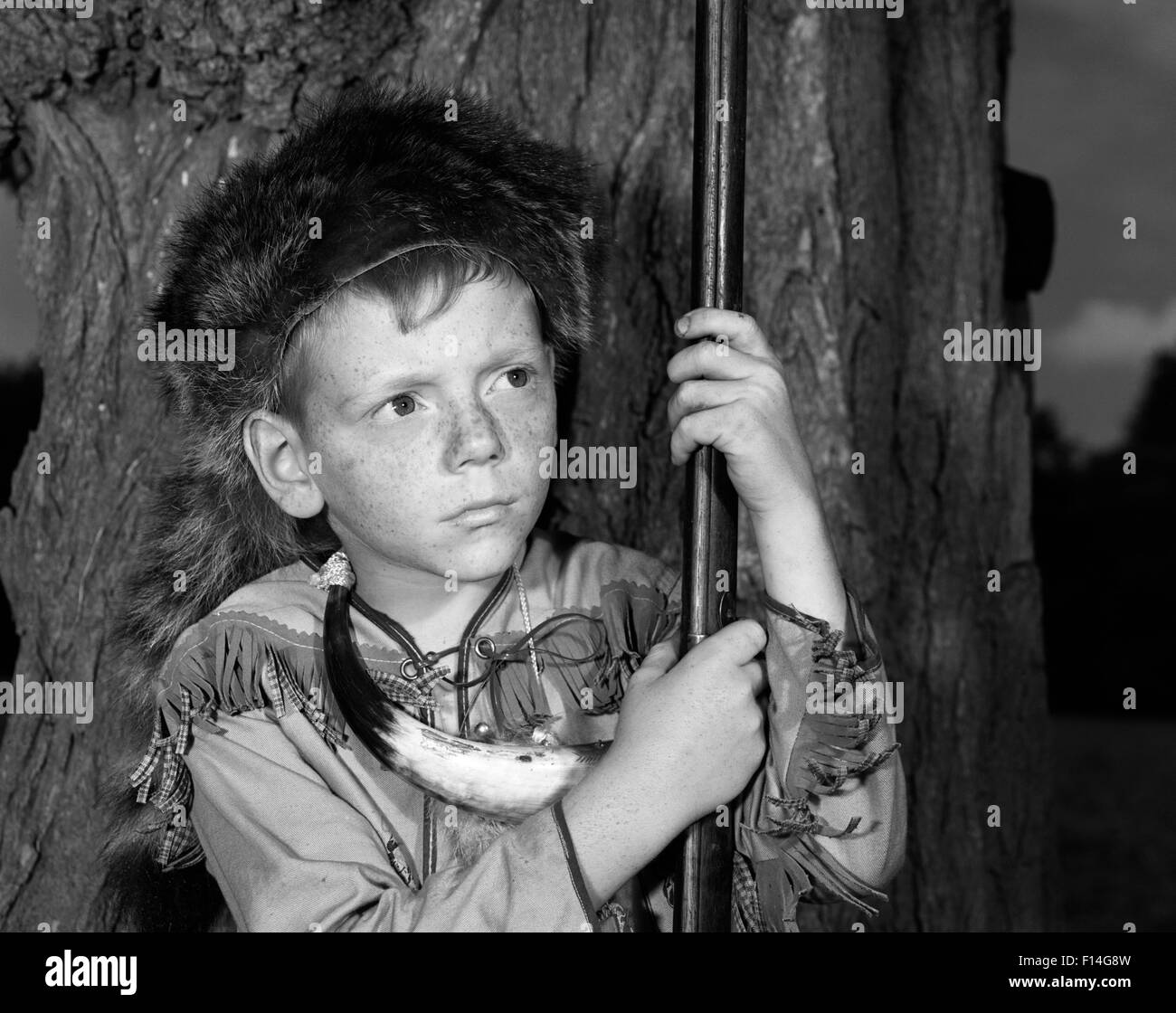 1950s BOY WEARING RACCOON SKIN HAT FRINGED WESTERN STYLE JACKET WITH POWDER  HORN AND ANTIQUE RIFLE bc7775b8544