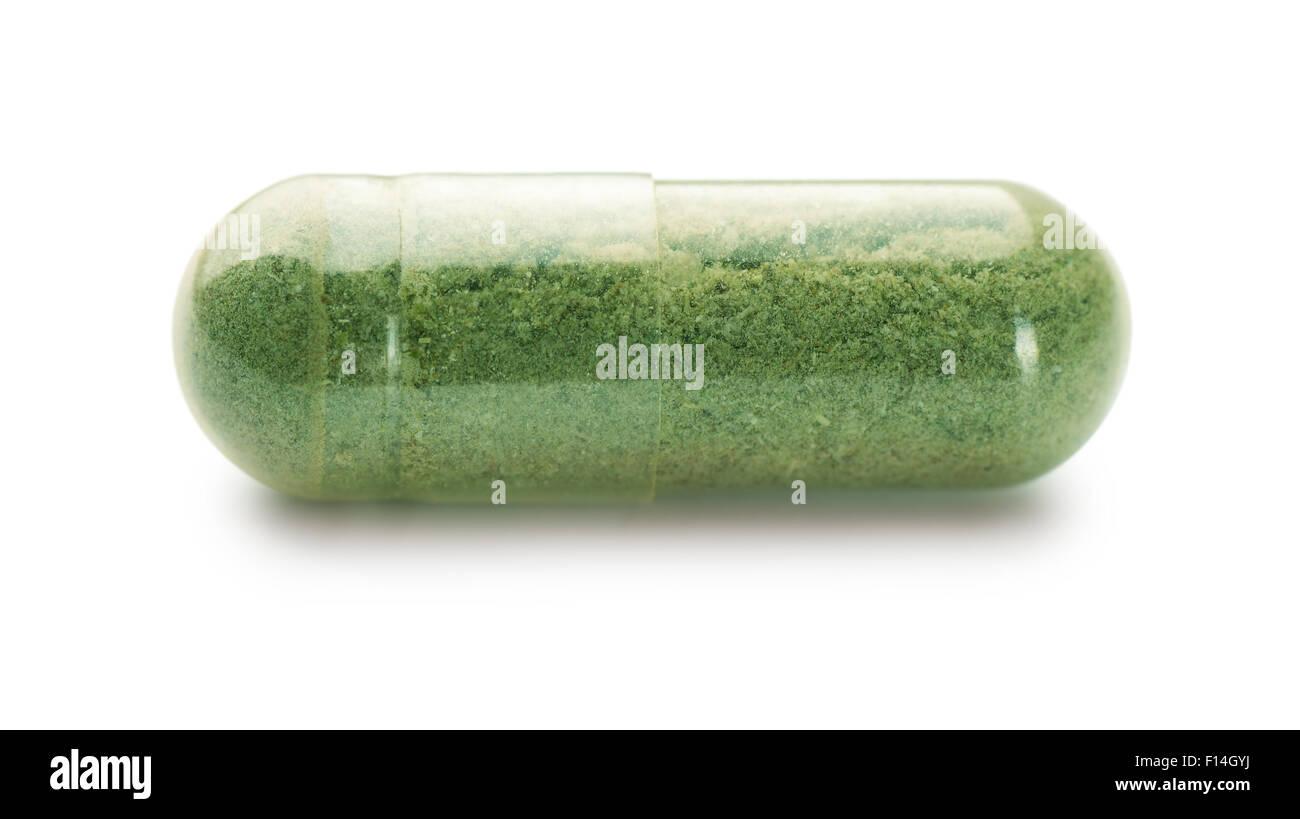 Single herbal capsule isolated on white - Stock Image