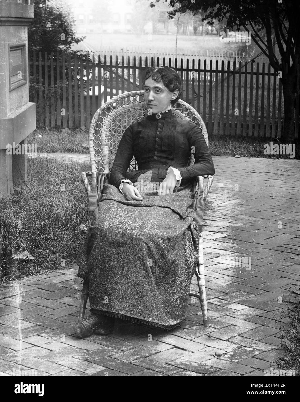 1890s 1900s TURN OF THE 20TH CENTURY PORTRAIT SEVERE WOMAN SITTING IN WICKER CHAIR IN BACKYARD BY HOUSE - Stock Image