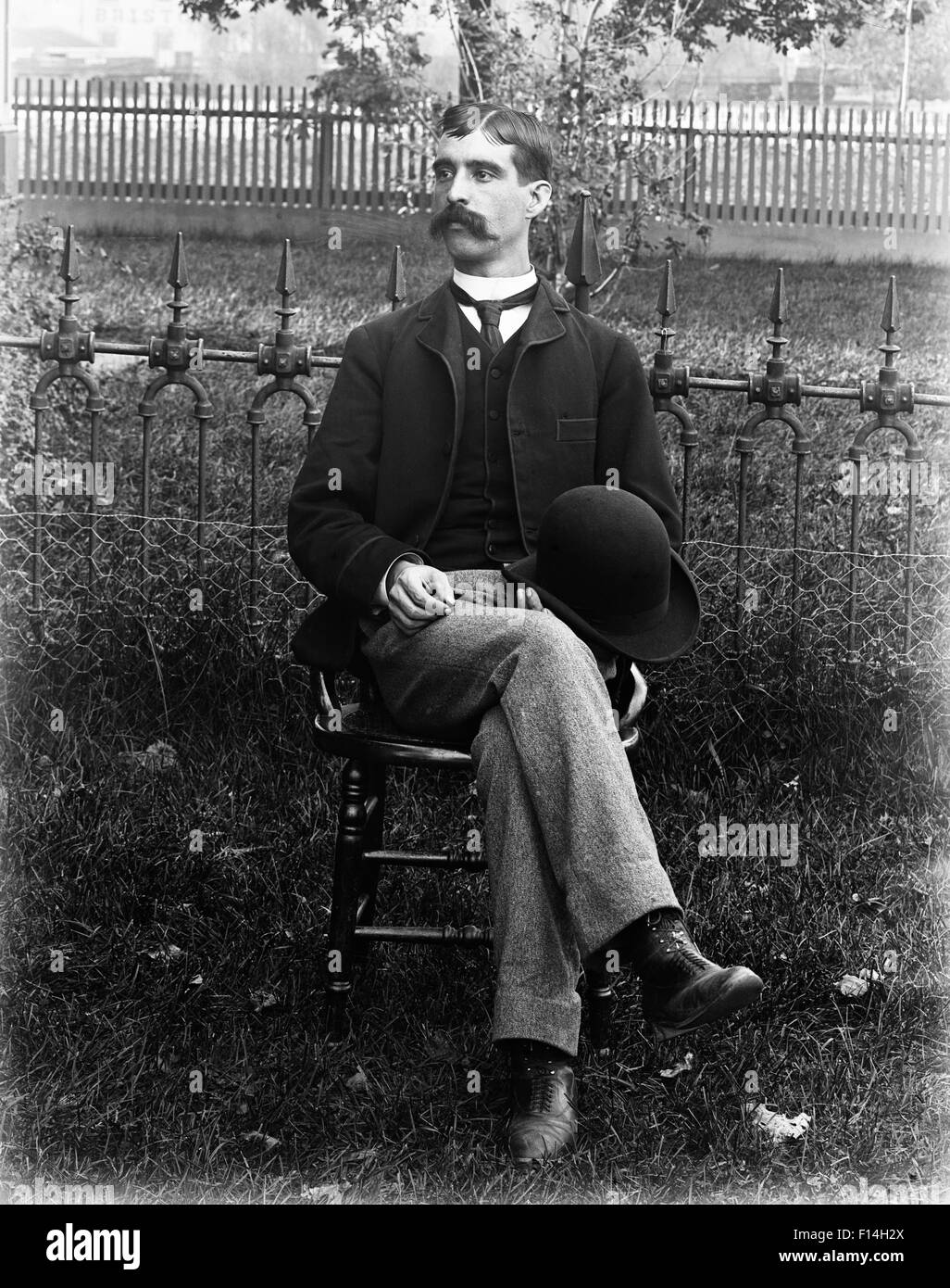1890s 1900s PORTRAIT MAN WEARING THREE PIECE SUIT SITTING IN CHAIR IN GARDEN HOLDING BOWLER HAT IN LAP - Stock Image