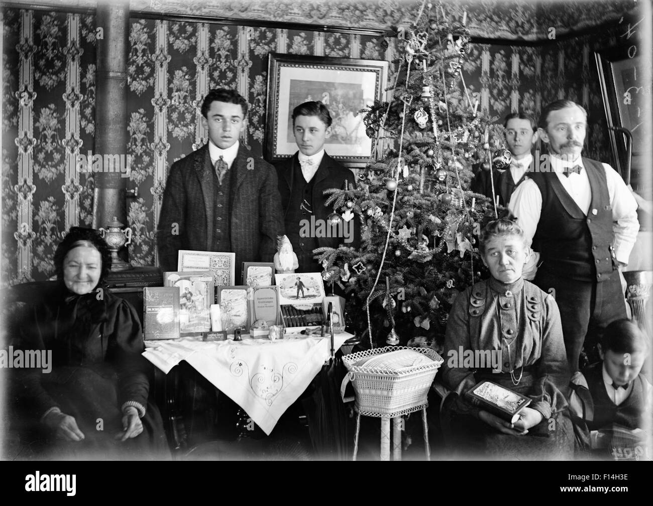 1890 1890s TURN OF CENTURY GROUP PORTRAIT FAMILY THREE GENERATIONS POSING  BY CHRISTMAS TREE GIFTS ON TABLE