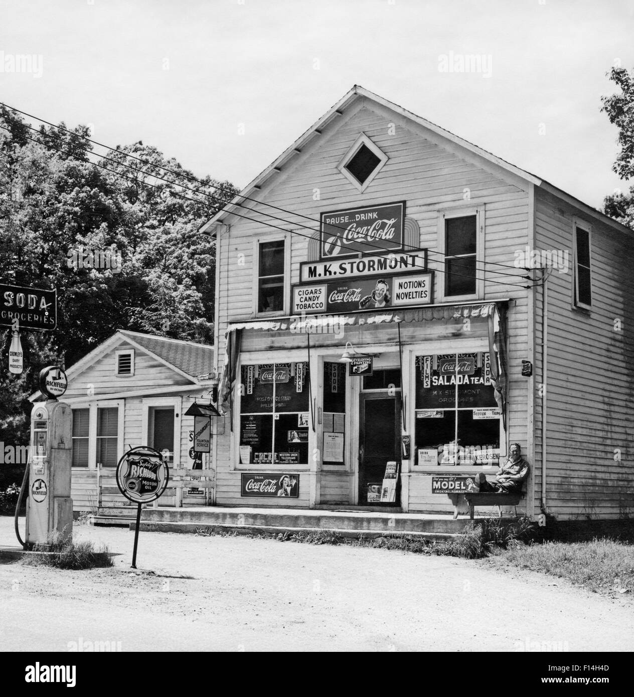 General Store Stock Photos General Store Stock Images: 1940s 1950s MAN STILLING ON PORCH GENERAL STORE AND
