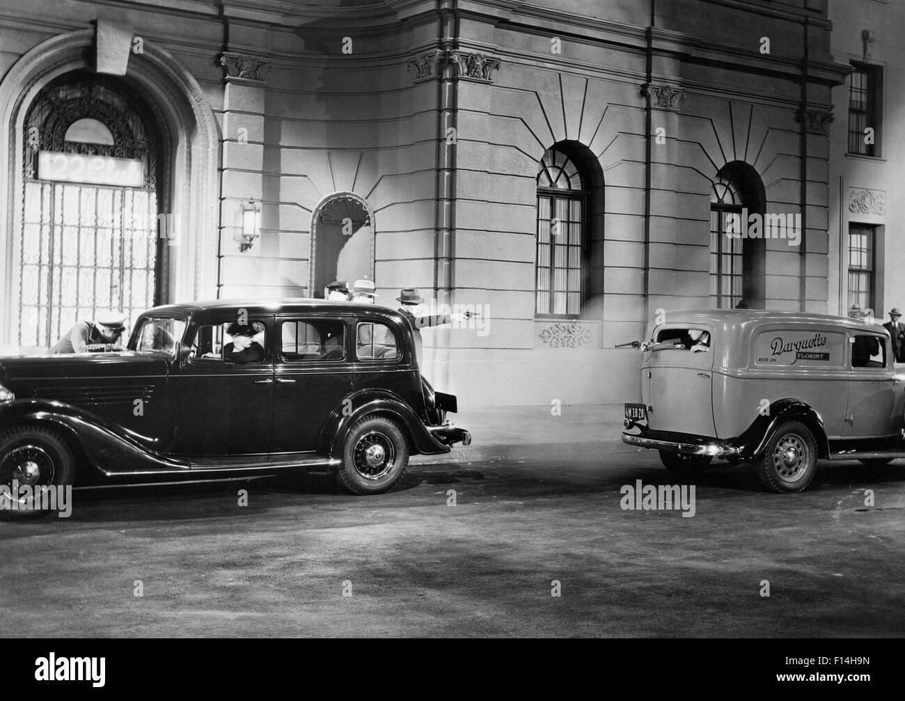 1930s MOVIE STILL OF NIGHTTIME SHOOTOUT BETWEEN GANGSTERS IN A PARKED CAR AND A PASSING PANEL TRUCK - Stock Image
