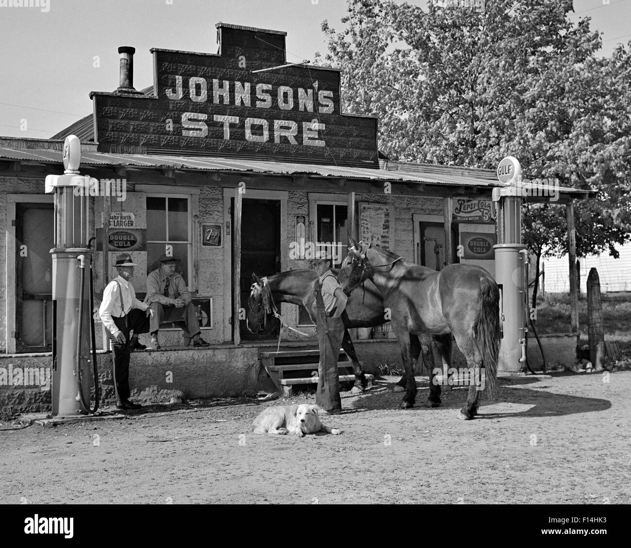 1930s GROUP OF THREE MEN TWO HORSES AND A DOG LOOKING AT CAMERA GATHERED IN FRONT OF COUNTRY STORE BRACKETED BY - Stock Image