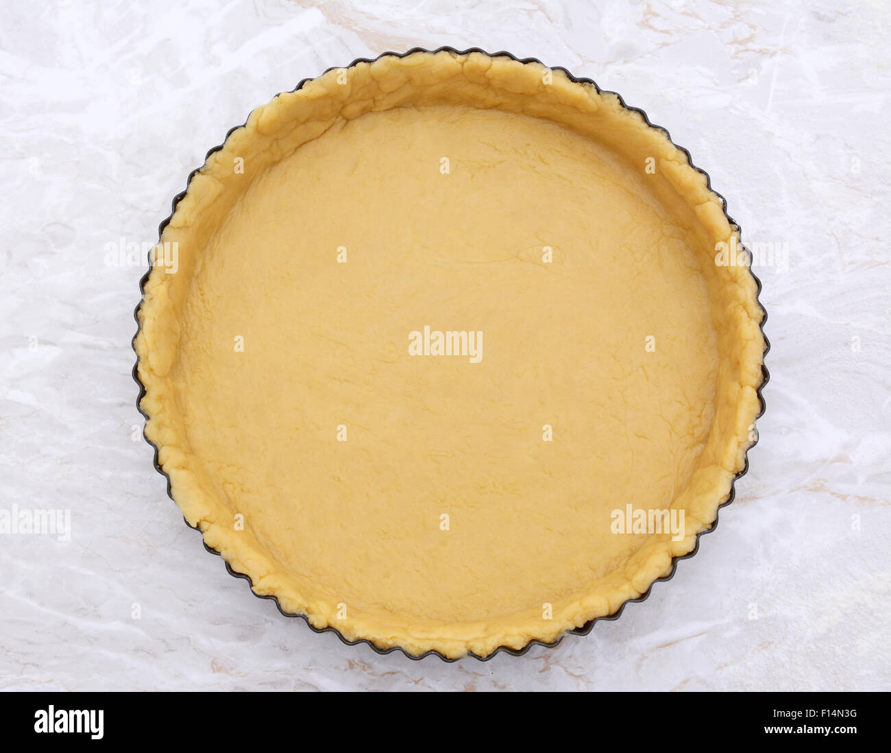 Circular metal flan tin lined with shortcrust pastry on a kitchen work surface - Stock Image