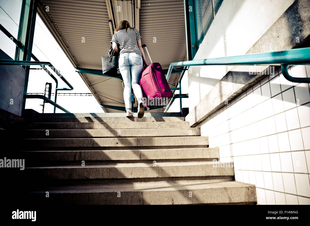 woman stepping on stairs with luggage at train station - Stock Image