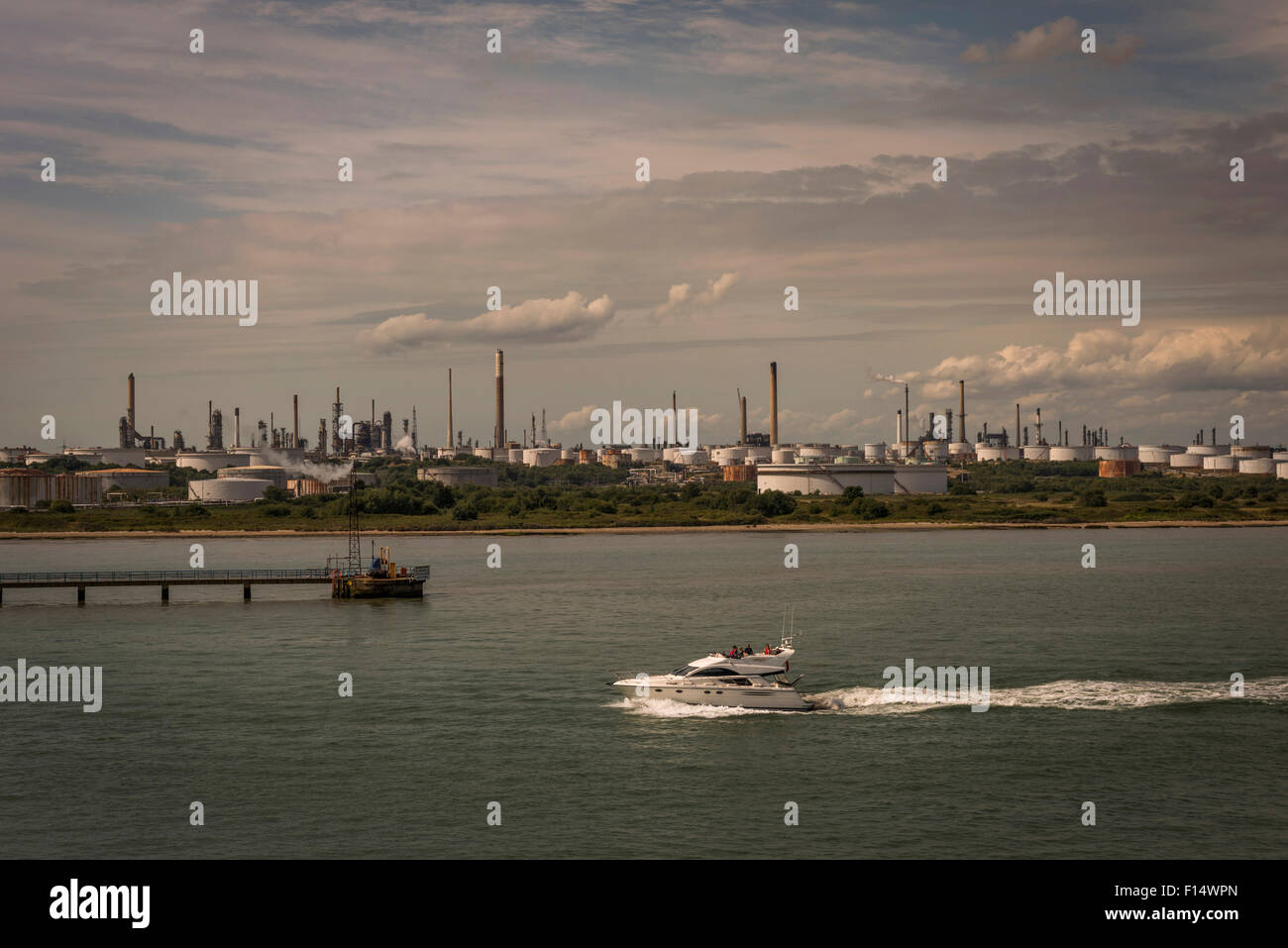 A motor launch passing Fawley Oil Refinery near Southampton, Hampshire, UK Stock Photo