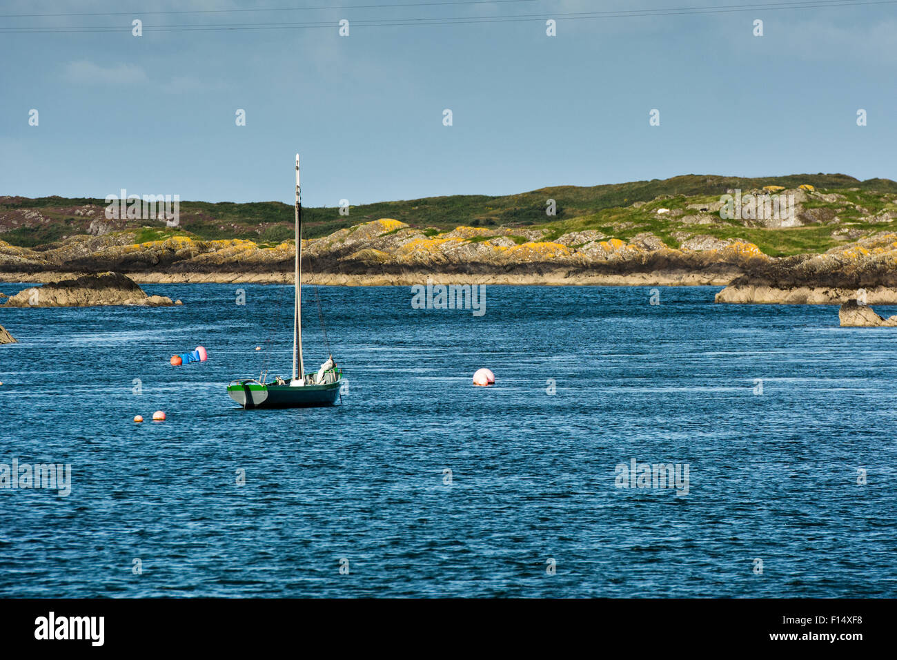 Summer coastal scene of rocky shoreline with moored sailing boat in cove of west Cork near Baltimore in Ireland - Stock Image