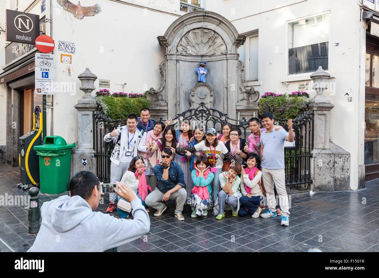 BRUSSELS, BELGIUM - AUG 22: Chinese tourists taking pictures at the Manneken Pis statue in Brussels. August 22, - Stock Image