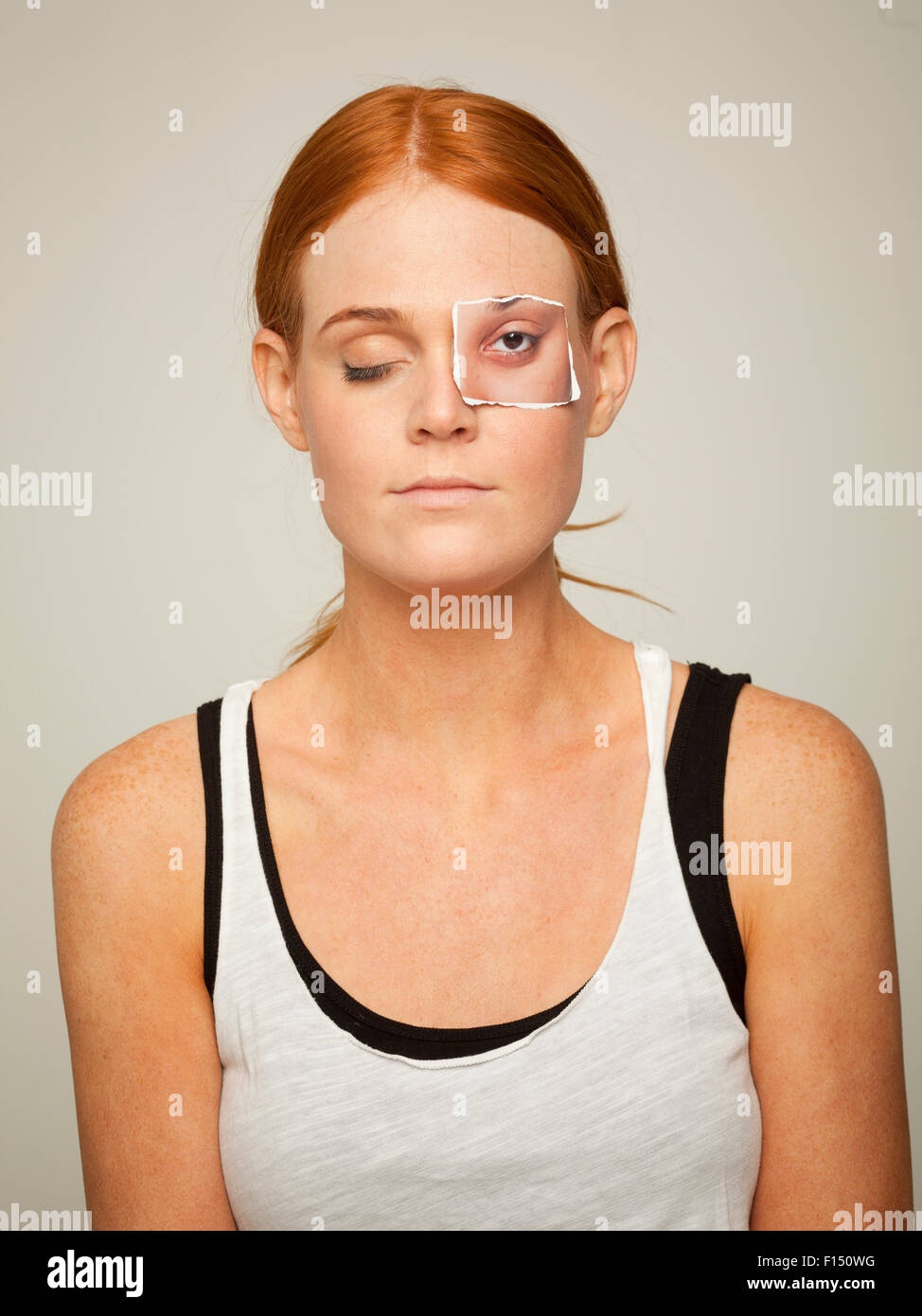 Studio shot of young woman wearing sleeveless top with artificial paper eye - Stock Image
