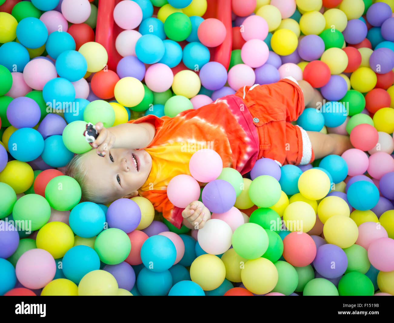 Cute kid boy playing with colorful balls Stock Photo