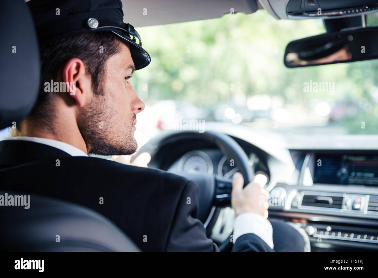 Portrait of a handsome male chauffeur riding car - Stock Image