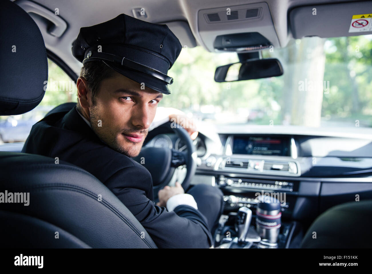 Portrait of a handsome male chauffeur sitting in a car Stock Photo