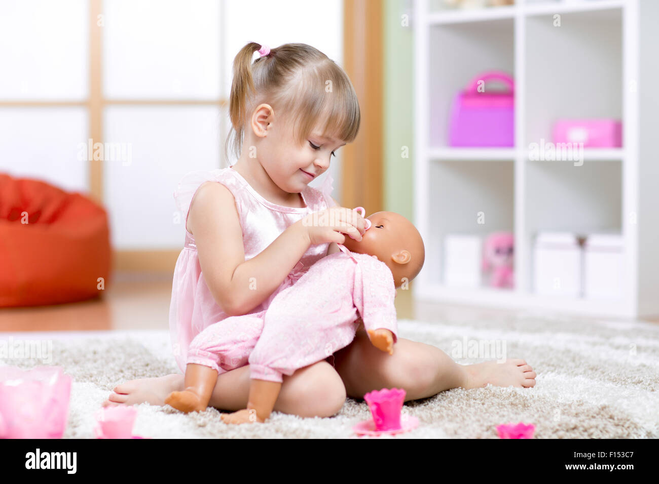girl playing with her baby-doll - Stock Image