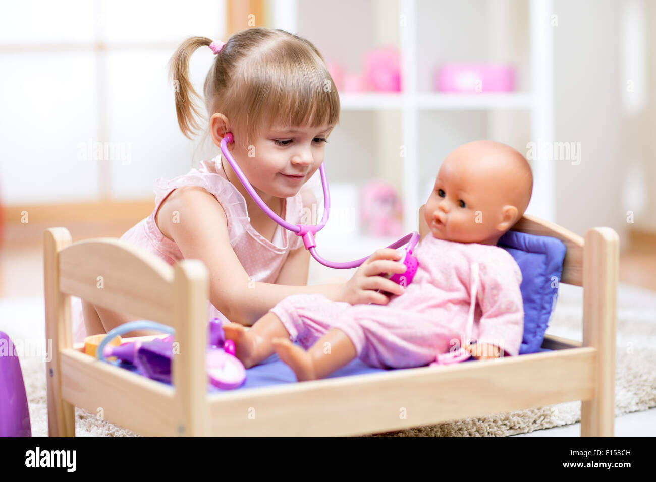kid playing a doctor with doll - Stock Image