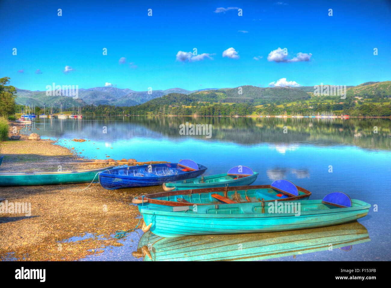Peace and calm a restful scene rowing boats on a lake with mountains The Lake District England UK at Ullswater - Stock Image