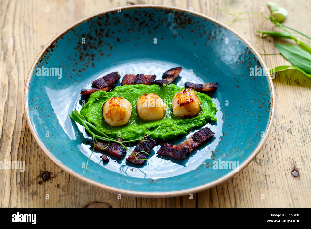 Scallops with pea puree and crispy bacon - Stock Image