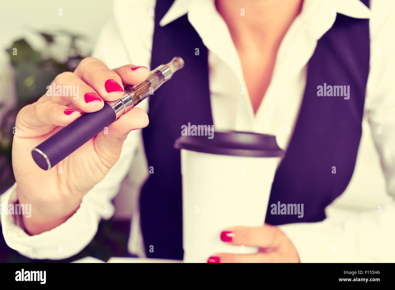 a young caucasian woman, with a cup of coffee in her hand, vapes from an electronic cigarette - Stock Image