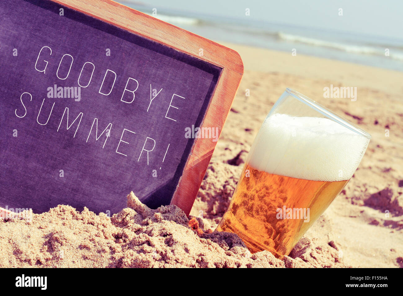 closeup of a chalkboard with the text goodbye summer written in it and a glass of beer, on the sand of a beach - Stock Image