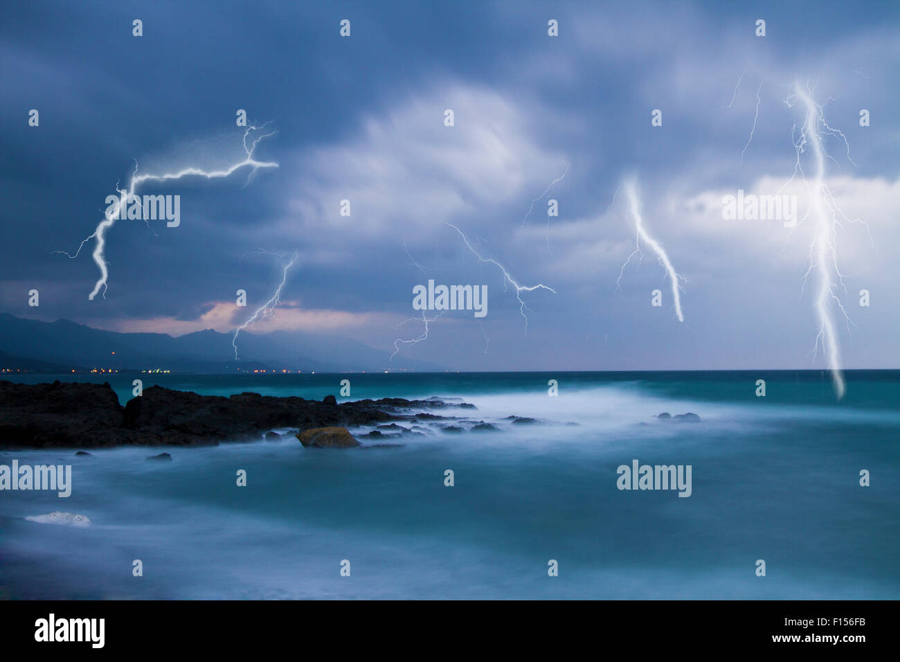 Lightning flashes across the beach from a powerful storm - Stock Image