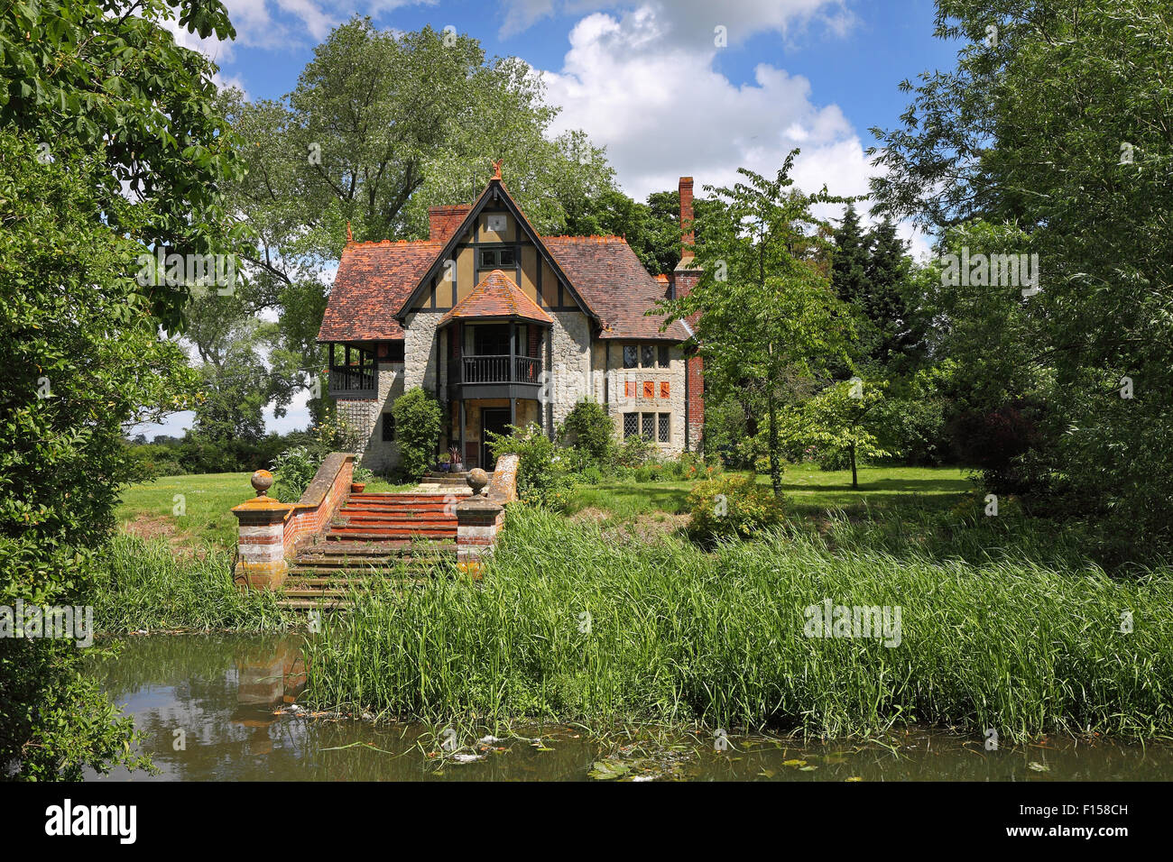 Quaint riverside english cottage with steps leading to waters edge - Stock Image
