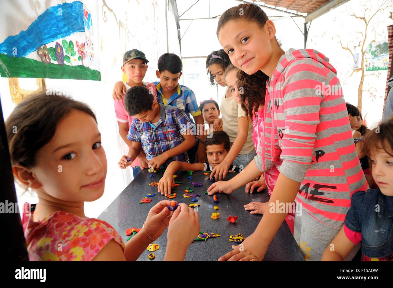 Damascus. 27th Aug, 2015. Syrian children play with plasticene during an extracurricular activity at a makeshift Stock Photo