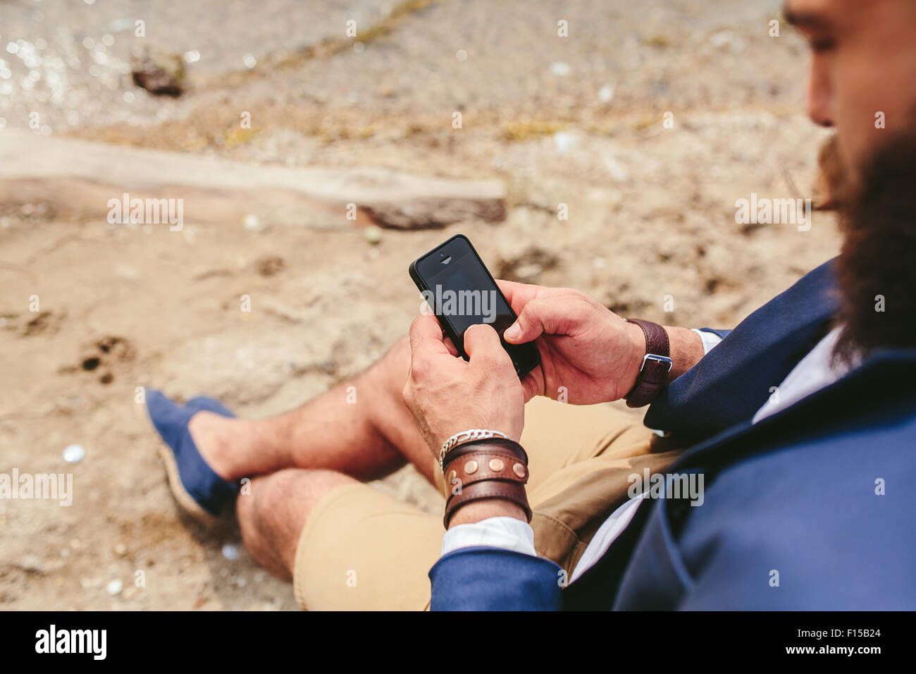 American Bearded Man using phone near the river - Stock Image