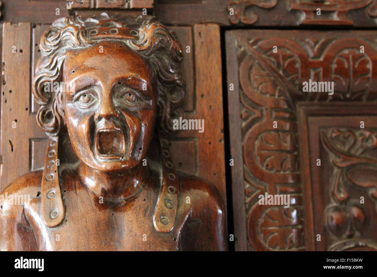 Medieval wood carving on cupboard door, of a man's face shouting, screaming, Renaissance Palace, Bourdeilles, - Stock Image