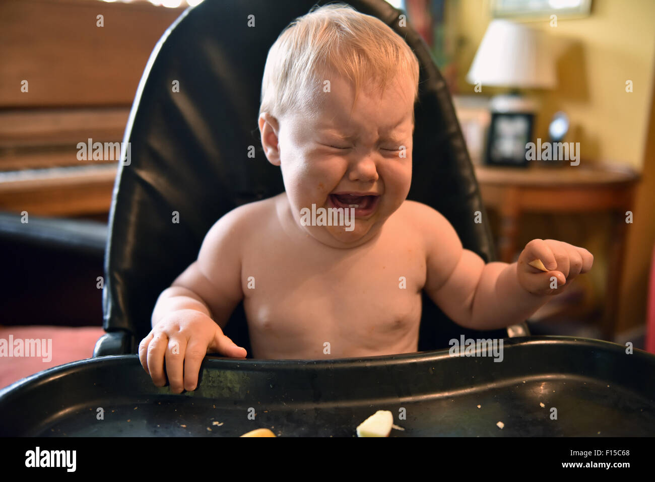 An eleven month old baby with a temperature sitting in her high chair crying. - Stock Image