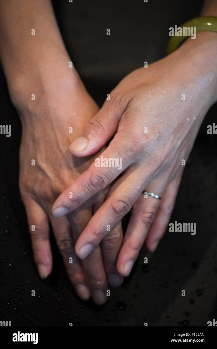 Hands of a woman under stream of tapwater - Stock Image