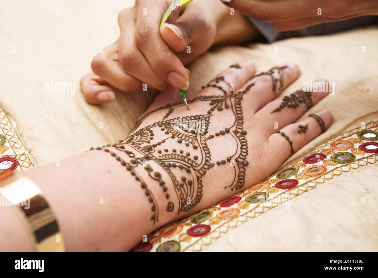 Henna patterns, hand being decorated / tattooed with hena. Henna painting. Henna hand decorations. - Stock Image