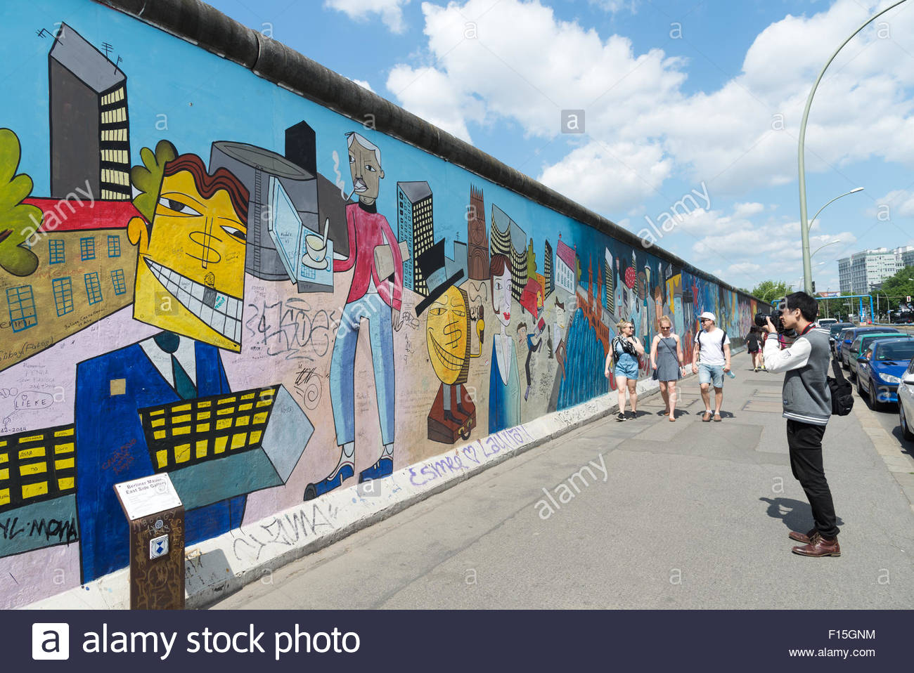 Tourist taking photos at the Berlin Wall East Side Gallery, Berlin, Germany - Stock Image