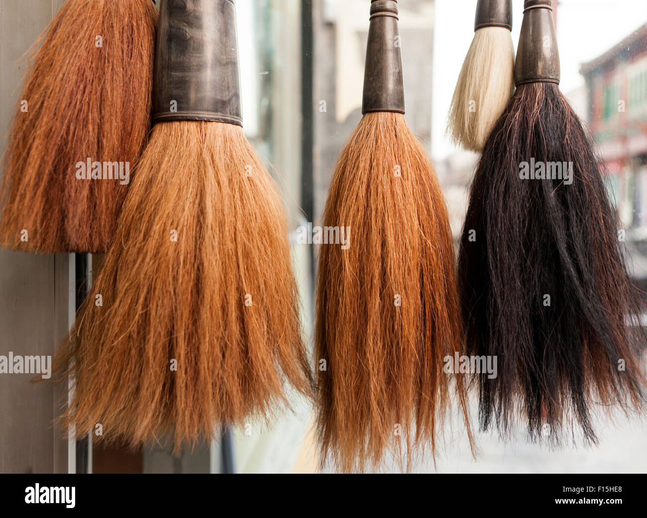 Calligraphy brushes hanging outside an artist supply store in a Beijing hutong - Stock Image